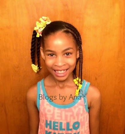 yellow beads and bows in this simple young girls hairstyle.