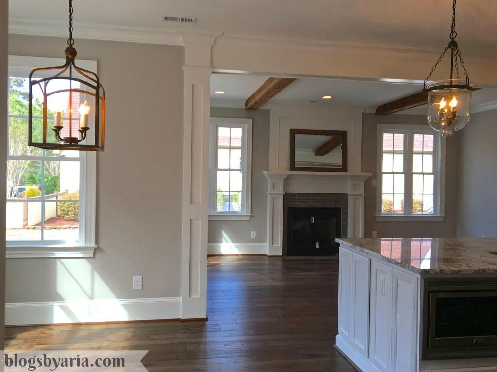 white kitchen views into morning room with wooden ceiling beams