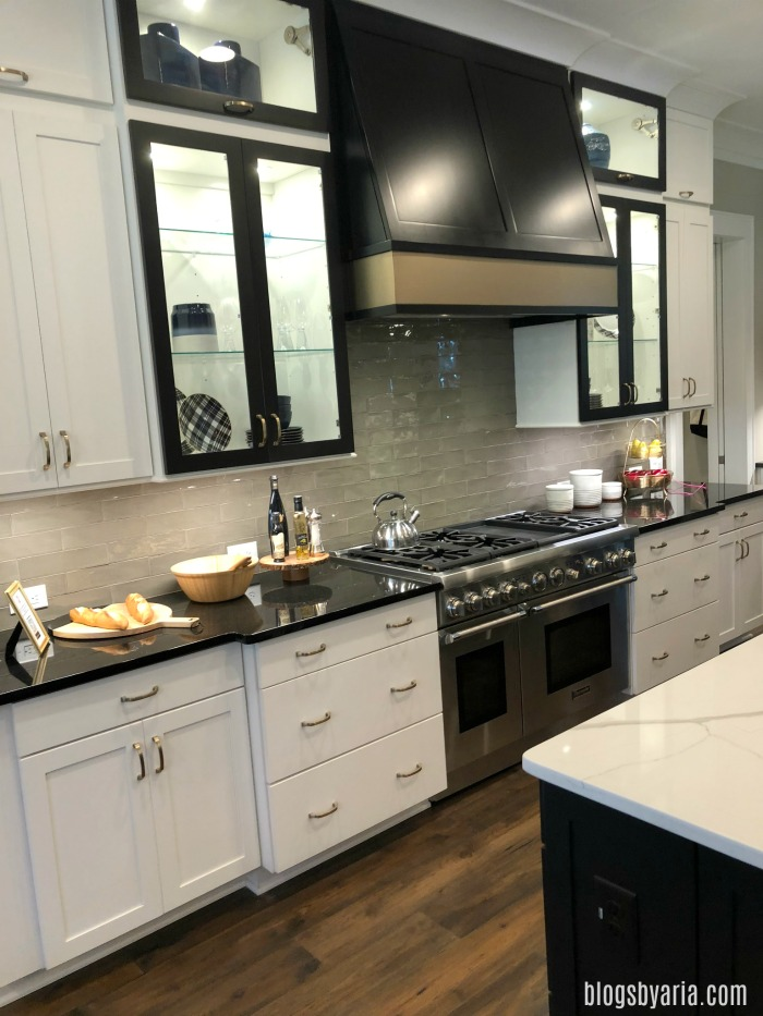 two toned kitchen with white cabinets and black range hood