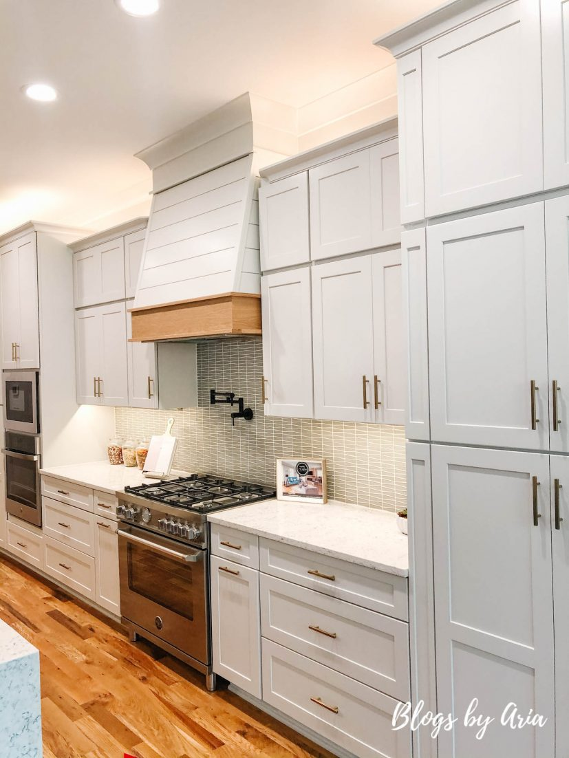 light gray painted kitchen cabinets with wood trimmed range hood