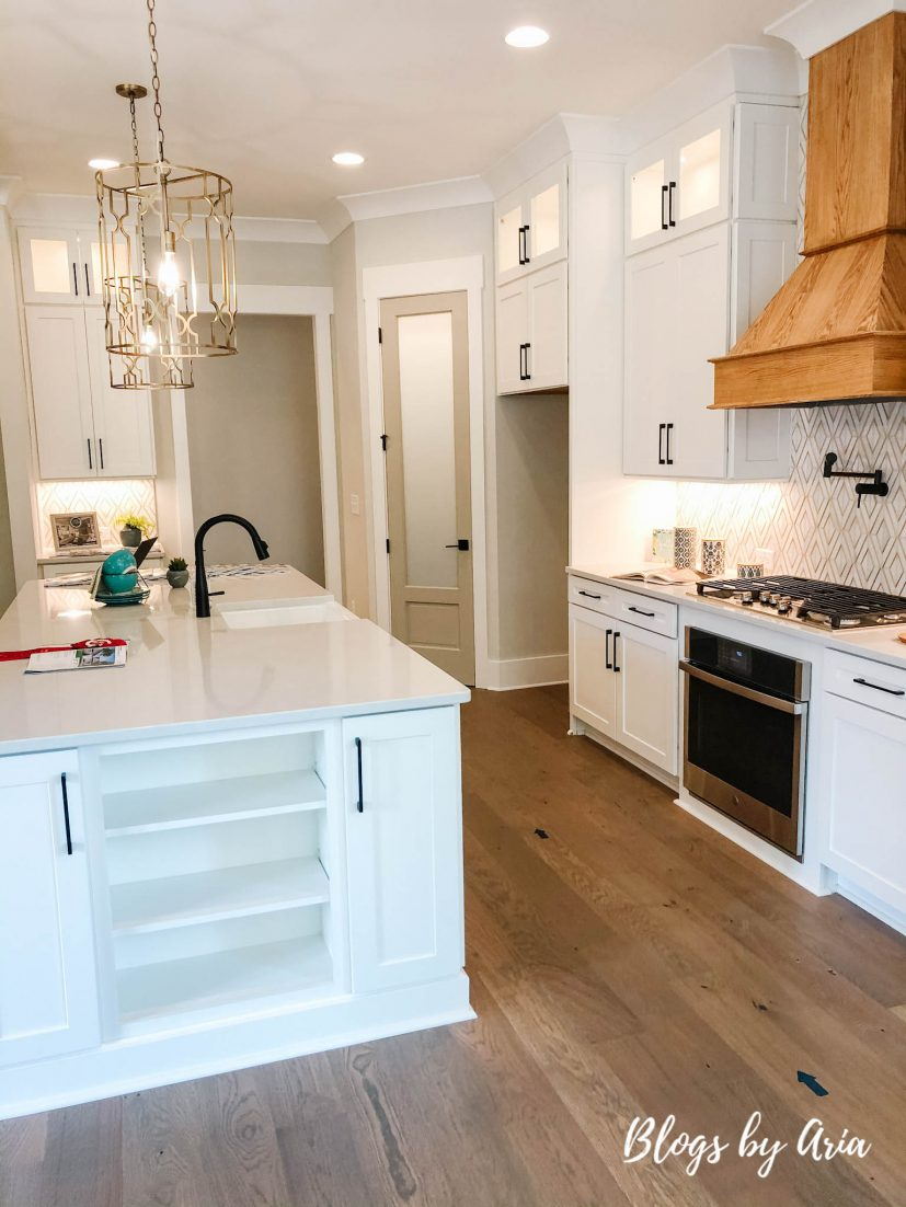 modern farmhouse kitchen with wood stained range hood