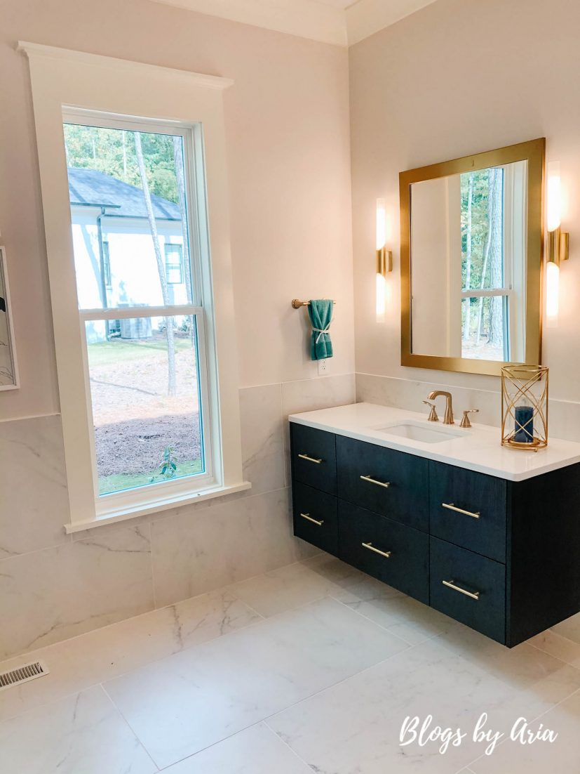 bathroom with black vanity and gold finishes marble floors