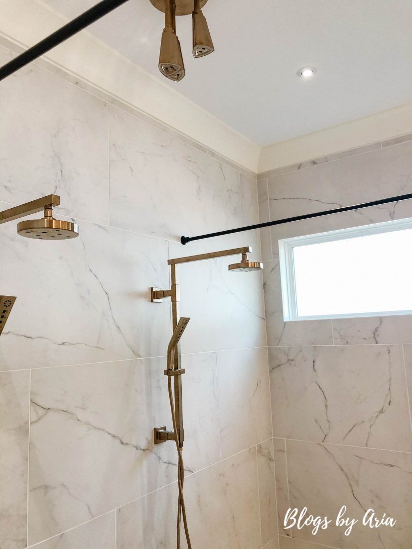 marble tiled walk through shower with gold hardware